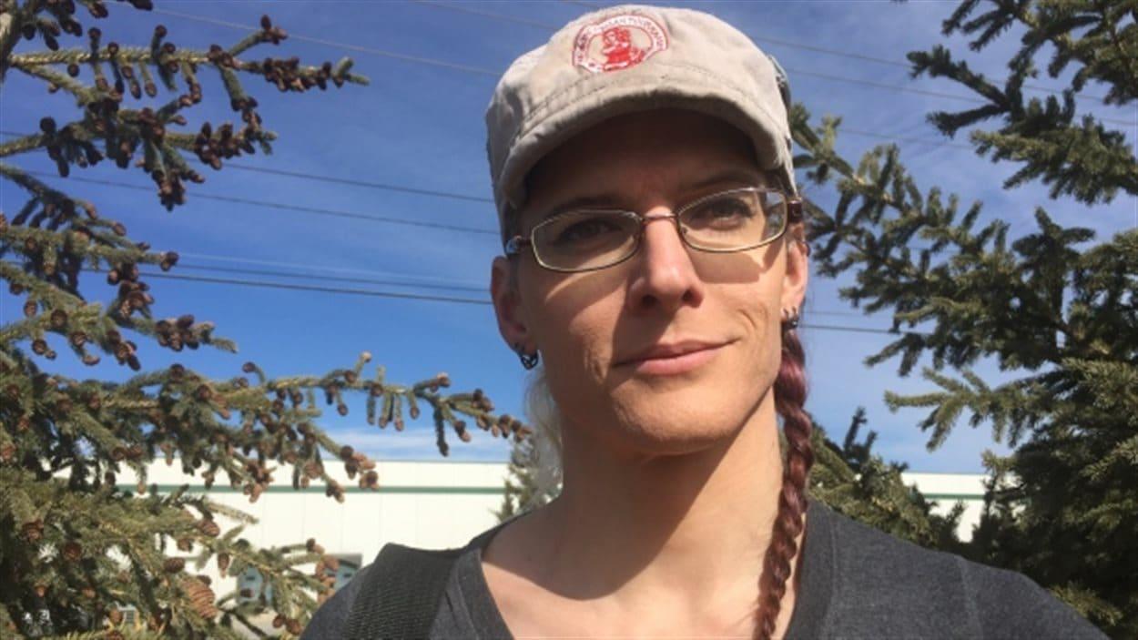 Une femme avec une casquette devant des arbres