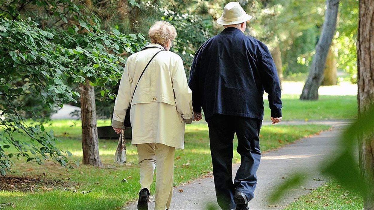 Un couple de personnes âgées se promènent dans un parc.