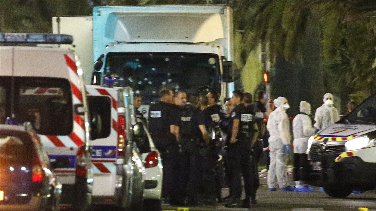 Des policiers et médecins légistes se tiennent à côté du camion qui a foncé sur la foule lors des célébrations de la Fête nationale française.