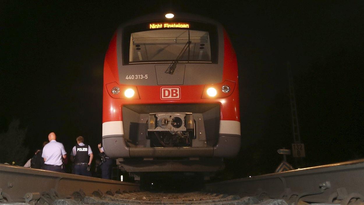 Des policiers près du train où est survenue une attaque à la hache.