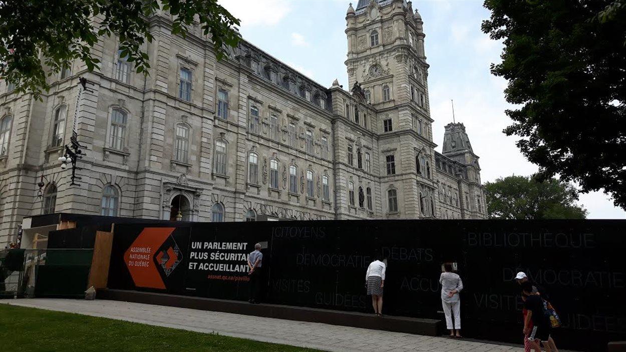 Des curieux s'arrêtent pour regarder l'évolution des travaux devant l'Assemblée nationale