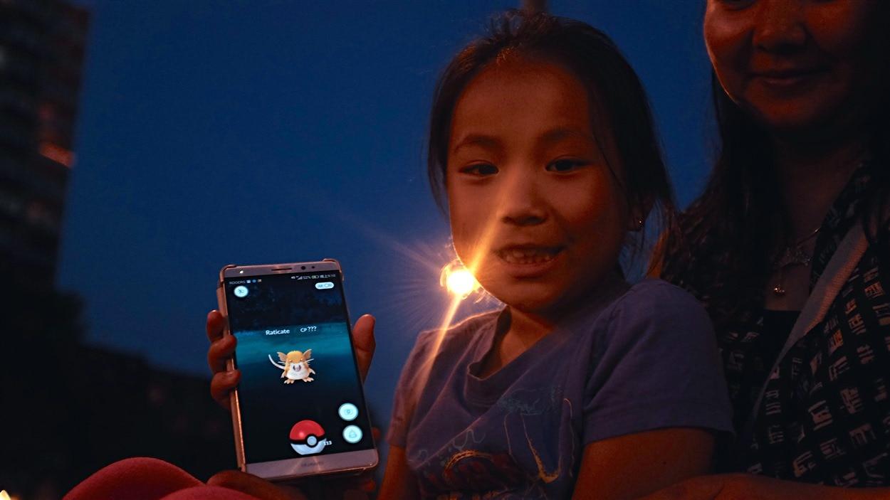 Une jeune joueuse vient d'attraper un Pokémon.