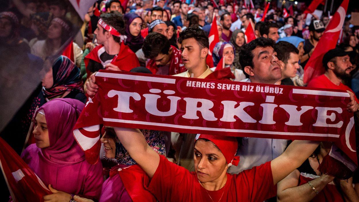 Une femme tient une bannière sur laquelle on peut lire : Turquie