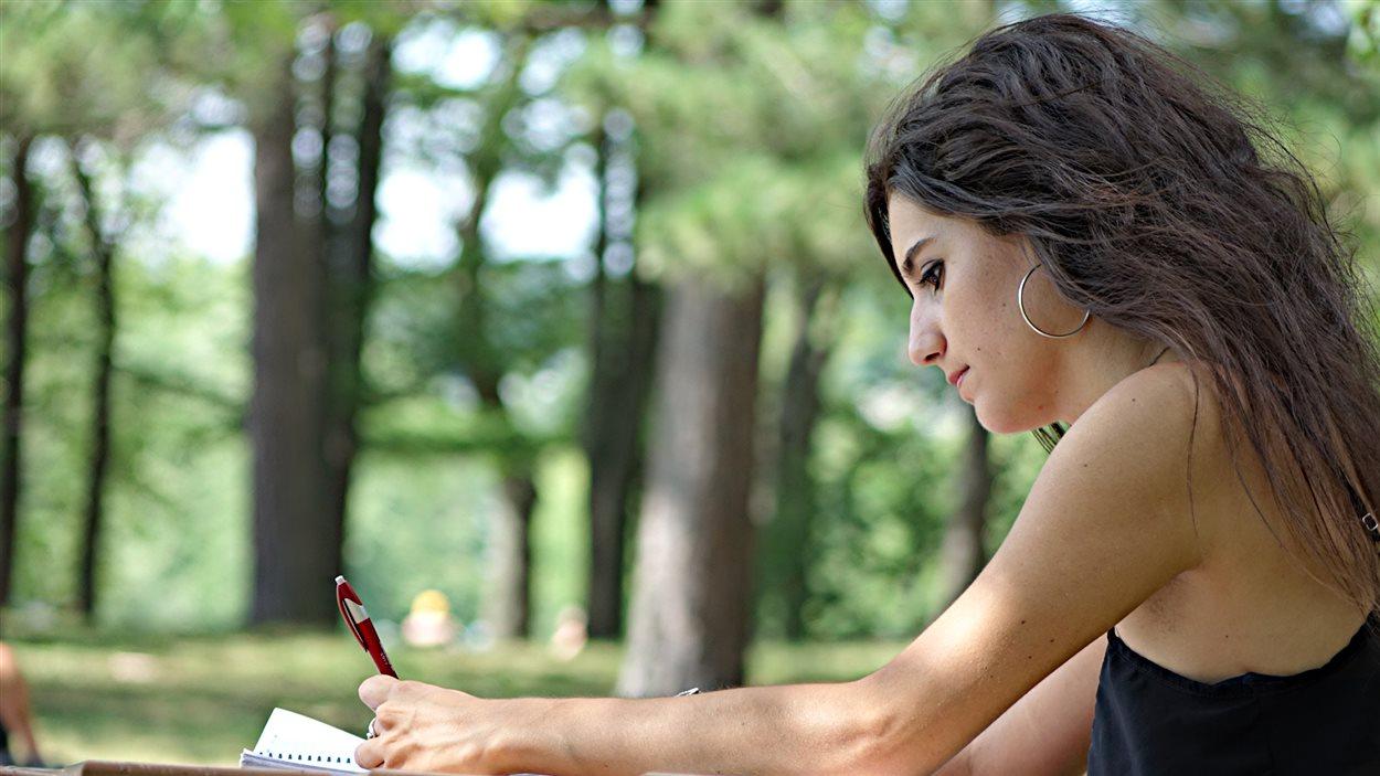 Mélanie Lemay, en train d'écrire à une table à pique-nique au parc Blanchard de Sherbrooke