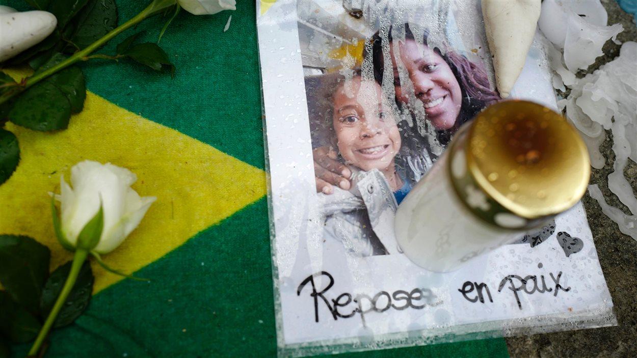 Une photo des deux victimes, un lampion et une fleur