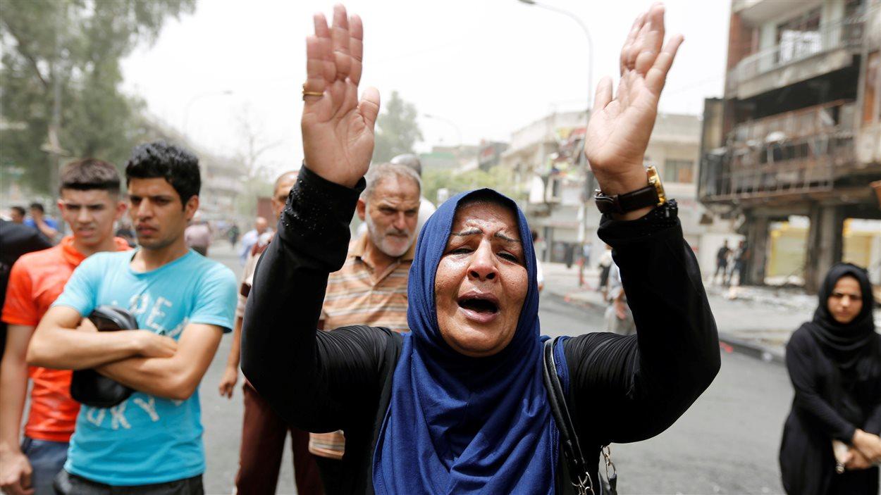 Une femme réagit le 4 juillet 2016 sur les lieux d'un attentat à la voiture piégée perpétré la veille dans une rue commerçante du quartier Karrada de Baghdad, en Irak.