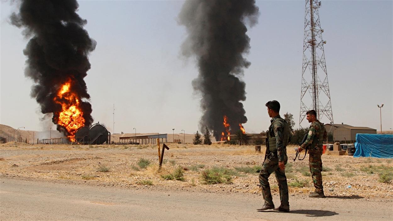 Des membres des forces kurdes regardent au loin la fumée s'élever de la station pétrolière Bai Hassan, attaquée par le groupe armé État islamique.