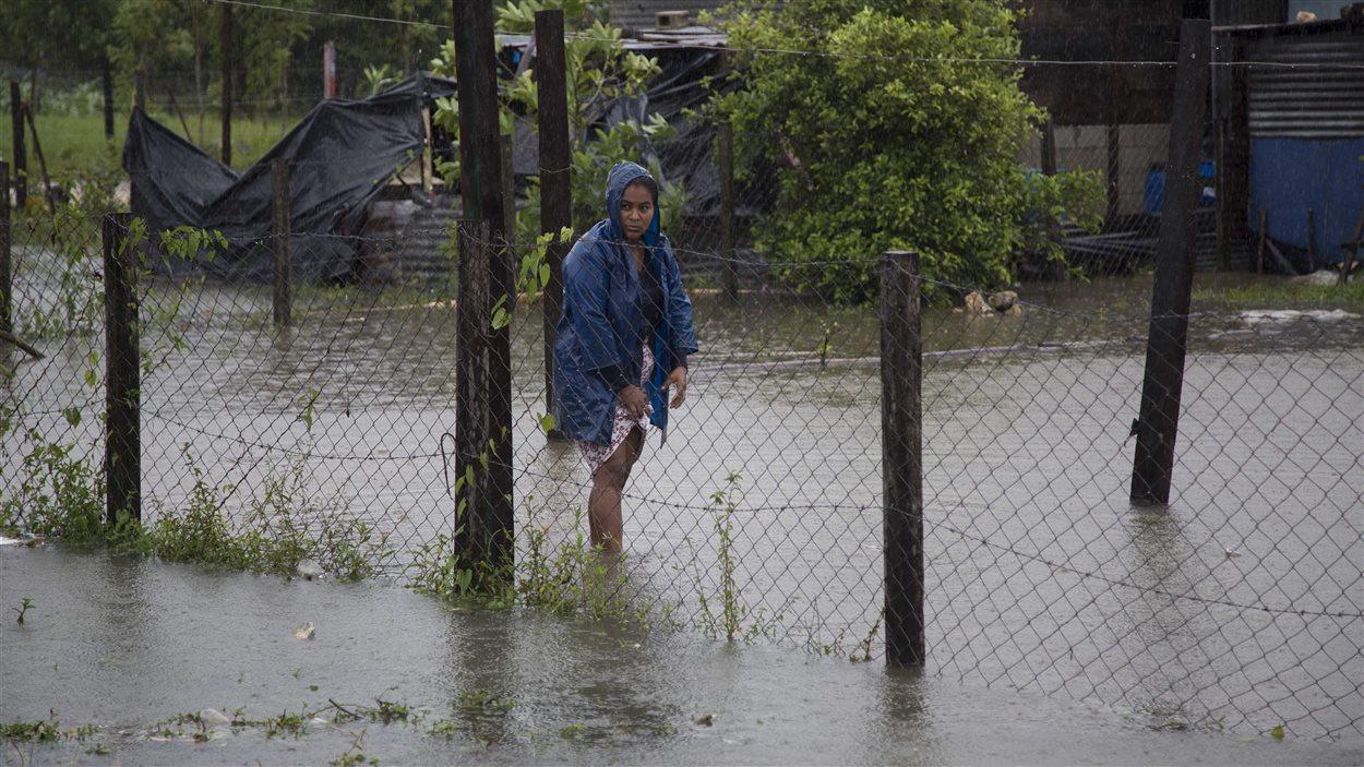 Une femme se promène dans des eaux de crues devant chez elle à Dolores, dans l'État guatémaltèque frontalier au Belize, le 4 août 2016.