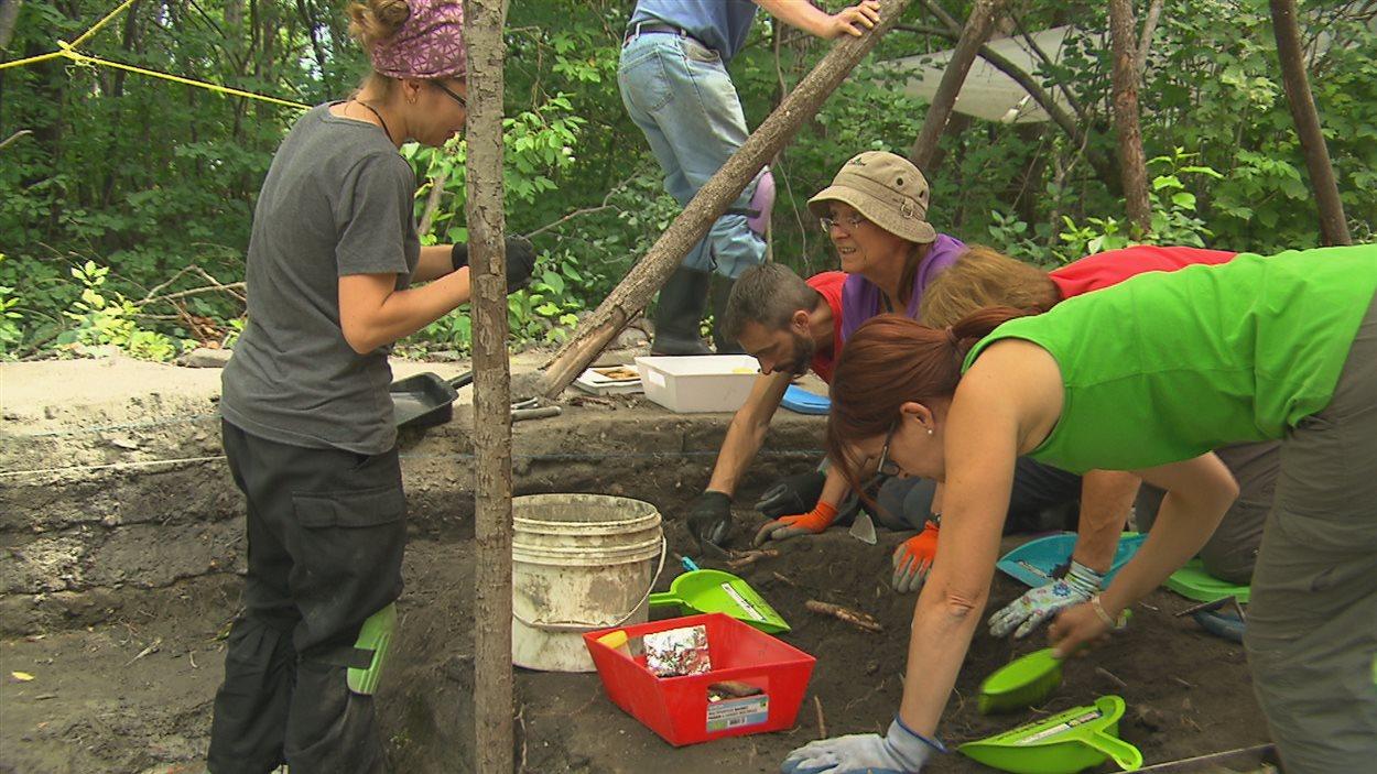 Des apprentis archéolgues s'initient à la fouille, dans le sol de l'ancien poste de traite de Chicoutimi.