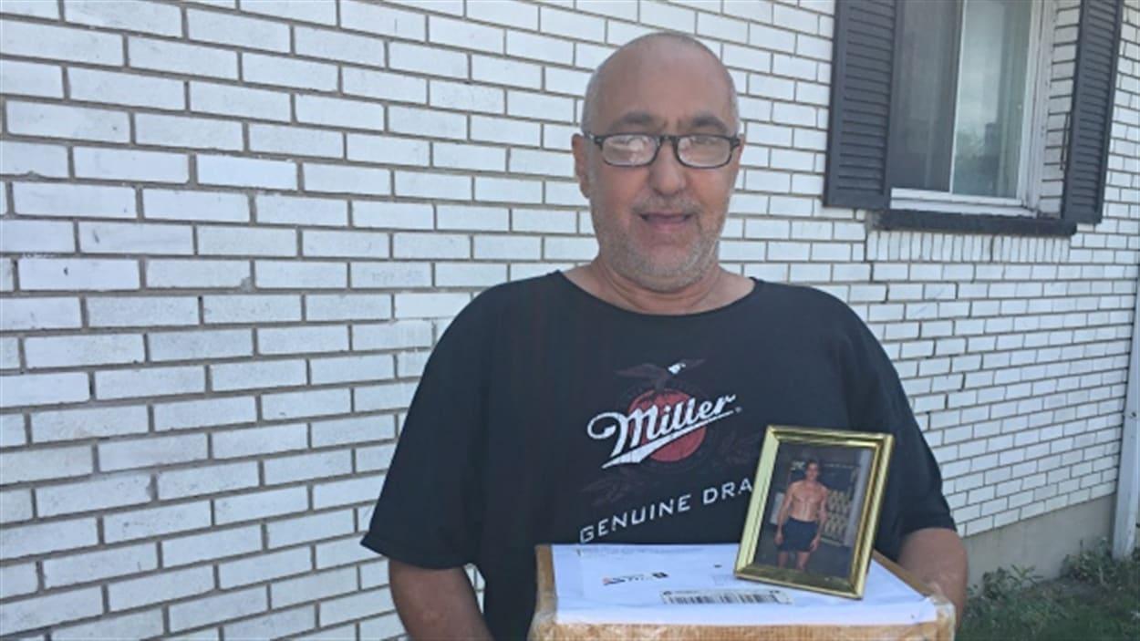 Joël Pinkus tient la boîte dans laquelle il y a les cendres de son frère.