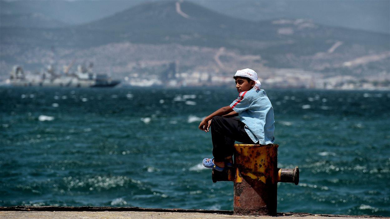 Un jeune migrant coincé dans le camp de Skaramangas en Grèce depuis l'accord UE-Turquie patiente au bord de la mer.
