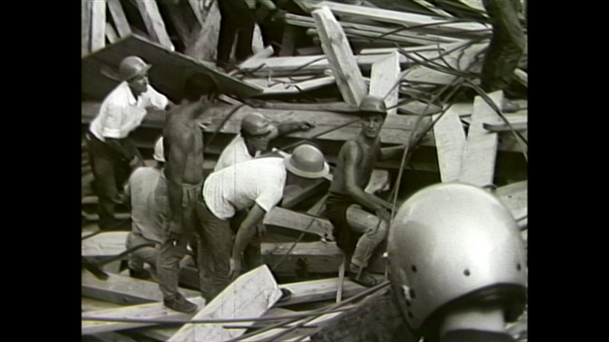 Des travailleurs tentent de porter secours aux victimes lors de l'effondrement du 10 août 1966.