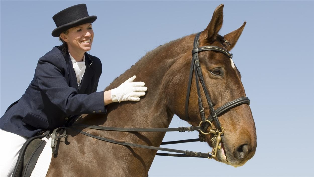 Une cavalière donne une tape sur le cou de son cheval.