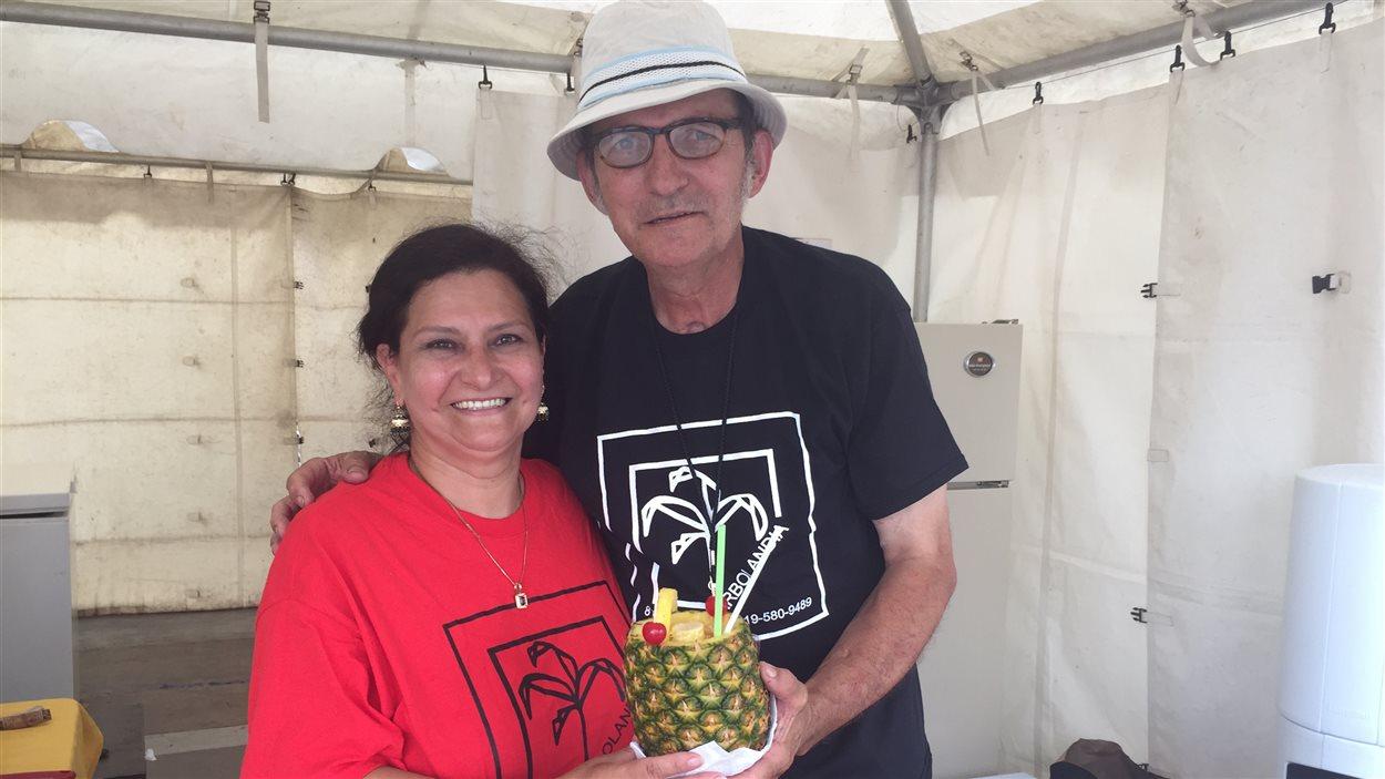 Alba Lucia et Francisco Javier Rodriguez, Colombiens d'origine, servent des piña coladas dans des ananas entiers au Festival des traditions du monde de Sherbrooke.