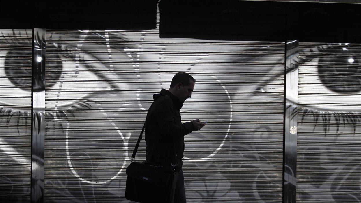 Un homme marche dans une rue devant une murale avec son cellulaire à la main, noir et blanc