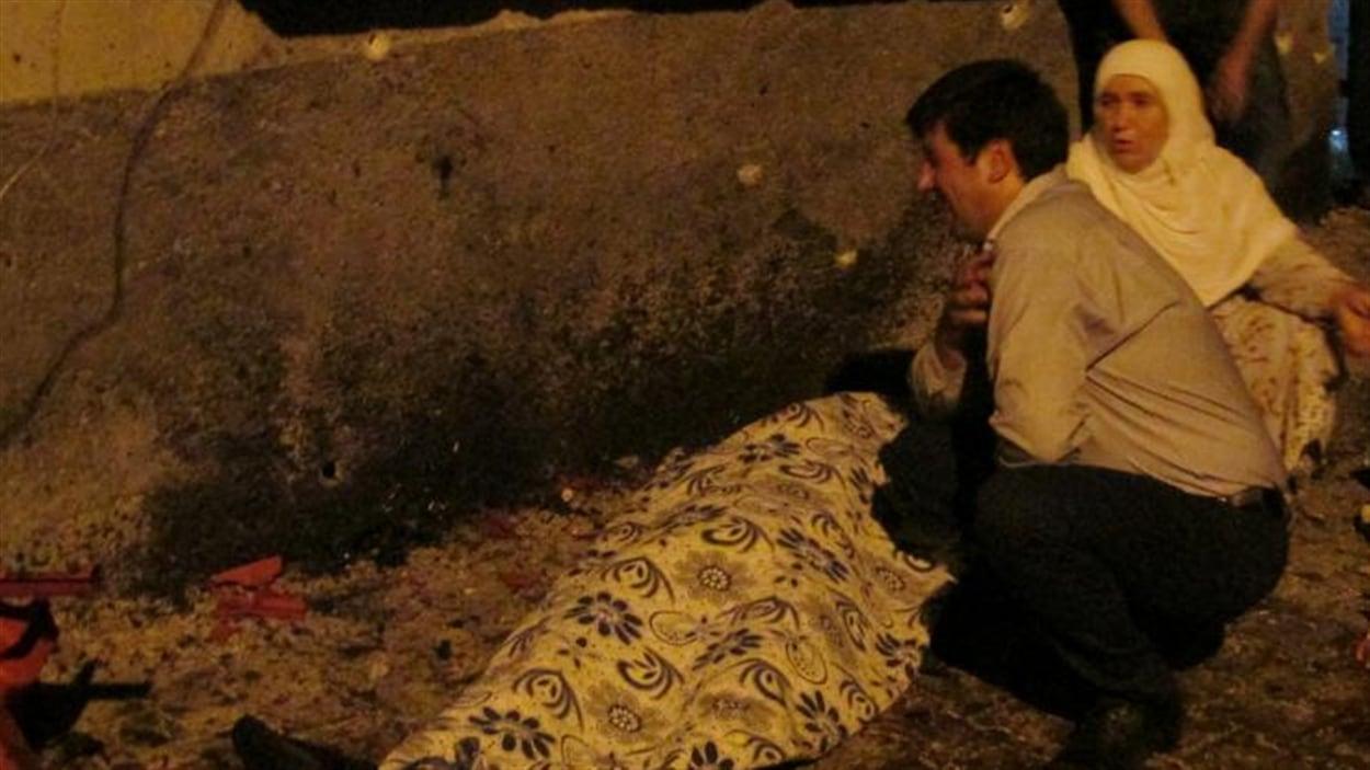 Un homme et une femme devant le corps de l'une des victimes de l'explosion d'une bombe à Gaziantep, en Turquie.