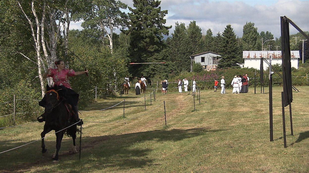 Femme qui tire à l'arc sur cheval au gallop. Yabusame signifie : cérémonie de l'arc