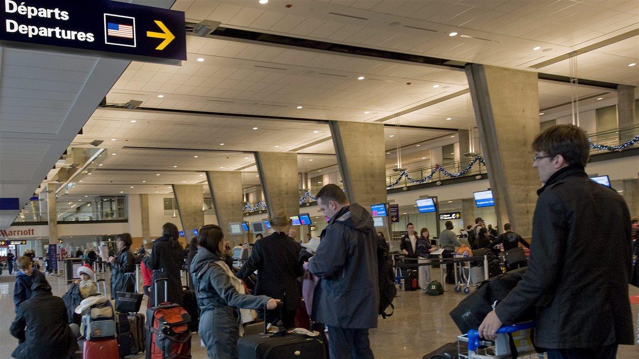 Des passagers font la file pour enregistrer leurs bagages à l'aéroport Montréal-Trudeau.
