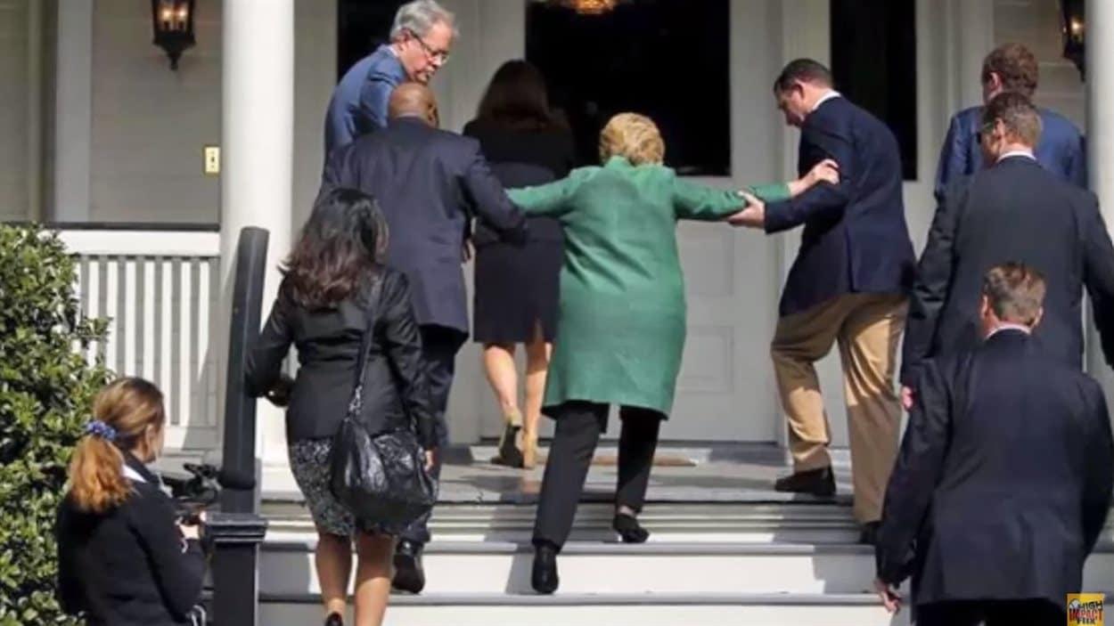 Hillary Clinton se fait aider pour monter les escaliers.