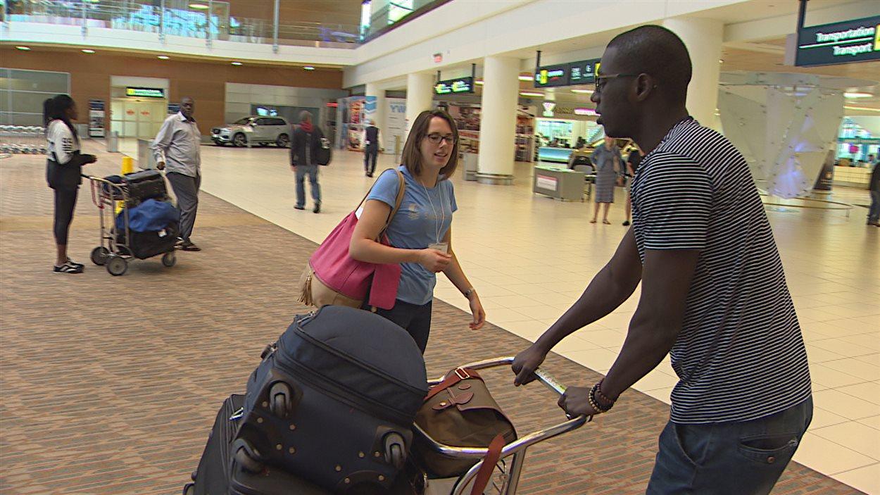 Amadou Samba Diop vient d'arriver à l'aéroport de Winnipeg. Il est accueilli par une étudiante de l'Université de Saint-Boniface.