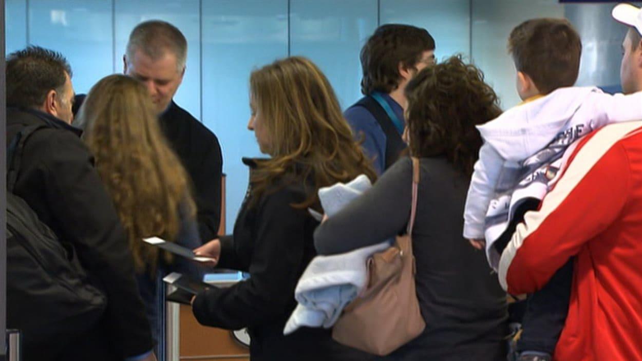 Plusieurs voyageurs font la file pour s'enregistrer à l'aéroport de Montréal.
