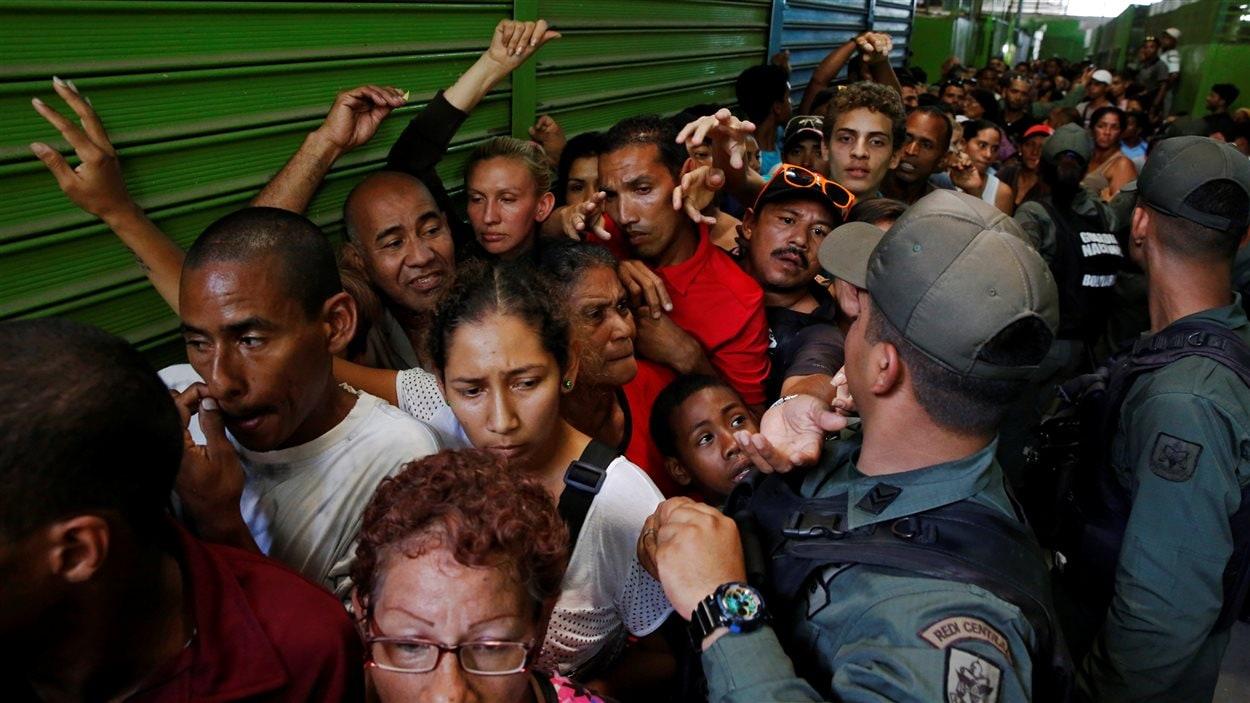 Les militaires vénézuéliens contrôlent la foule alors que les gens font la file pour se procurer de la nourriture.