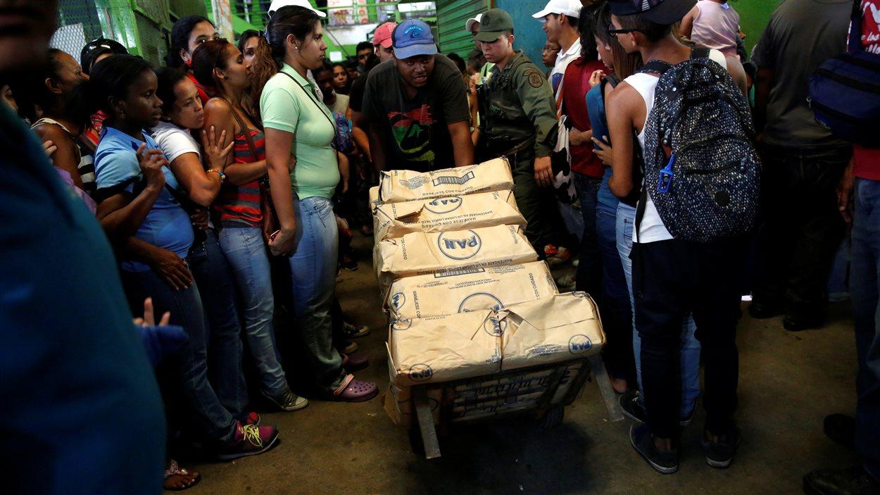 Un travailleur vénézuélien transportant des paquets de farine de maïs traverse une foule venue chercher de la nourriture.