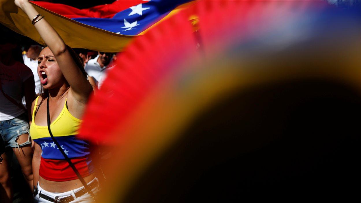Une manifestante tient un drapeau du Venezuela pendant un rassemblement pour réclamer un référendum pour demander la révocation du président Nicolas Maduro.