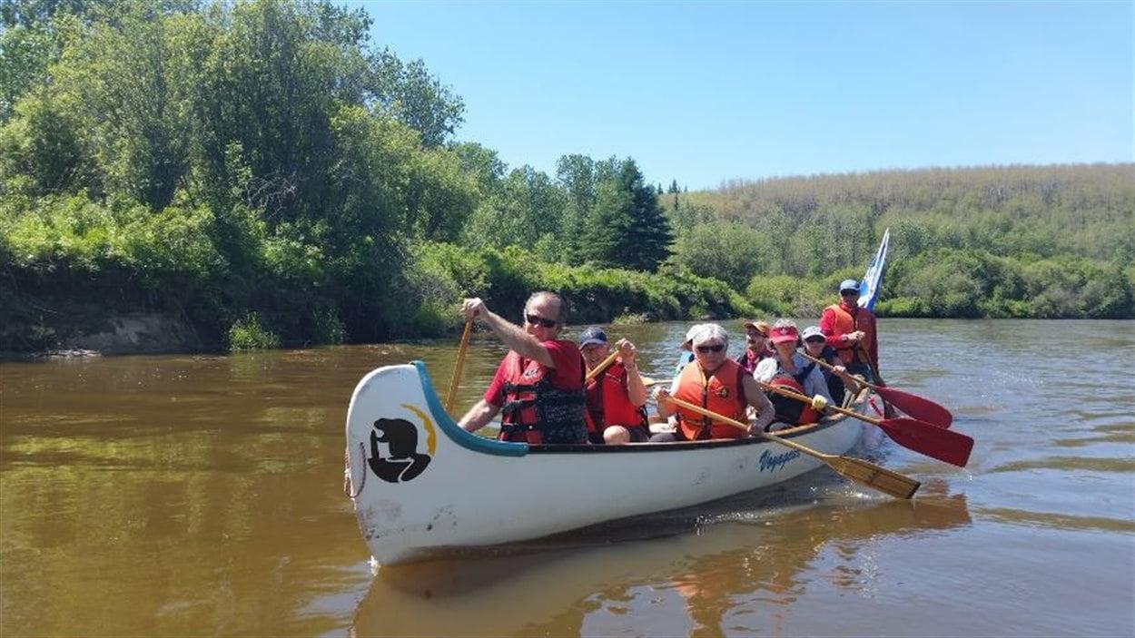 """L'équipage de huit pagayeurs de Bonnyville avance sur la rivière Sand dans le canot """"Le Beaugrand"""" avec le gouvernail René Champagne."""