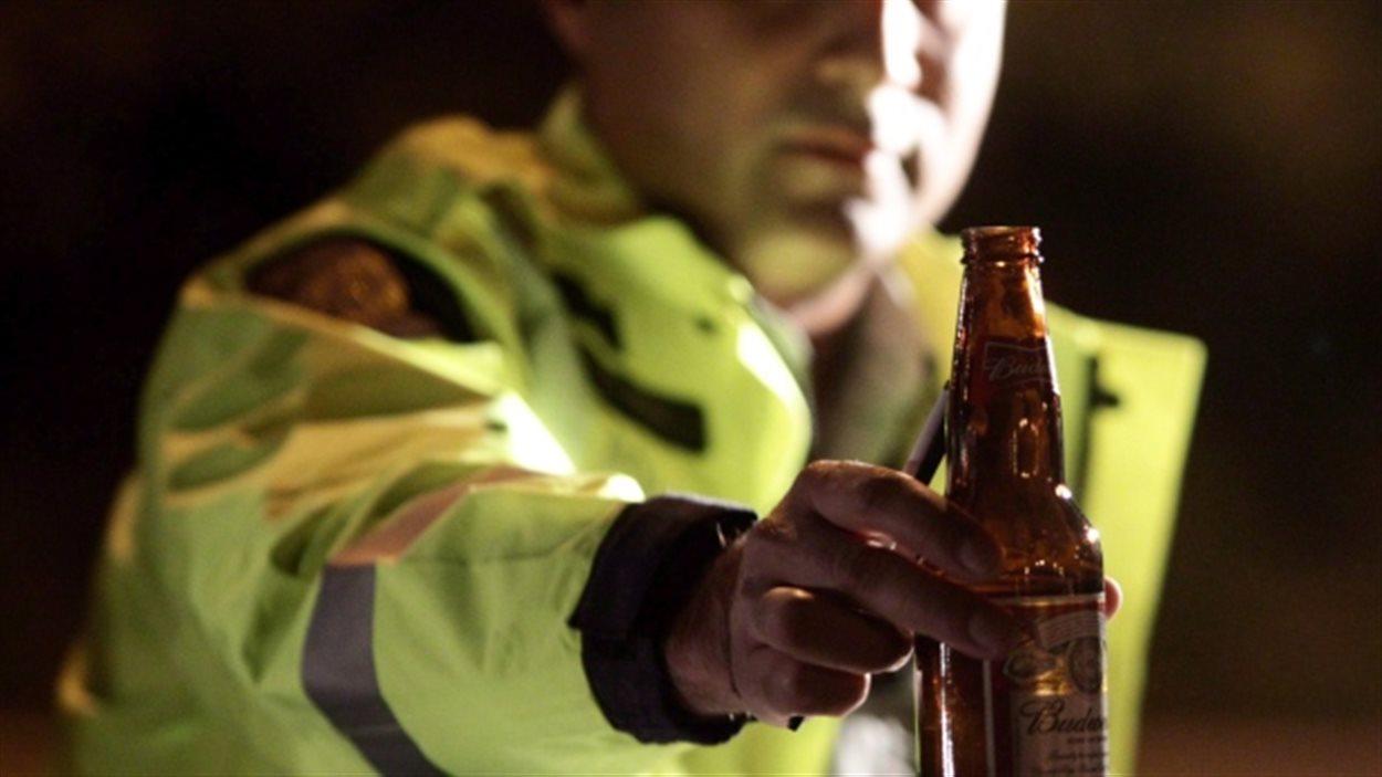 Un agent de la GRC confisque une bouteille de bière ouverte dans un véhicule lors d'un contrôle routier.