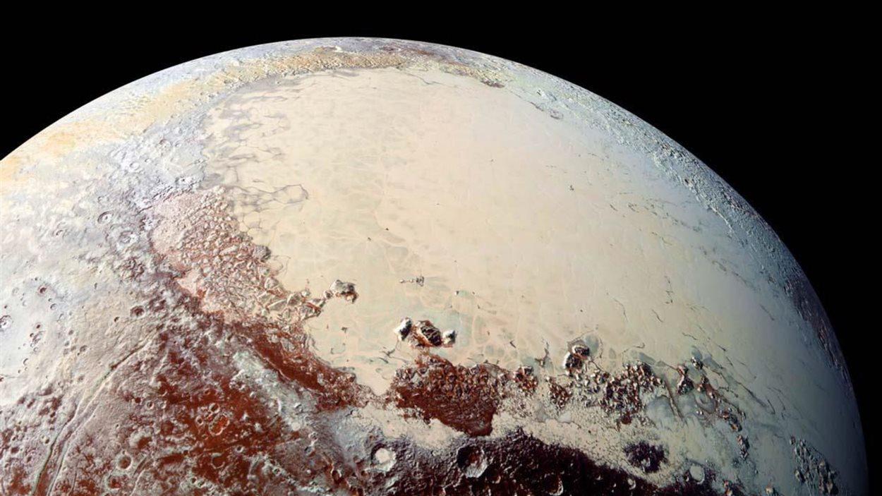 La calotte de glace de « Sputnik Planum », en fausse couleur, est entourée de montagnes.