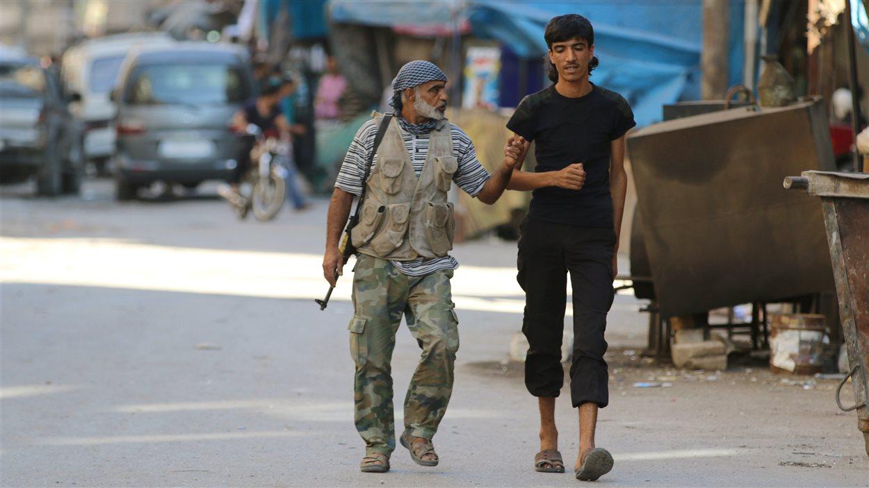 Des combattants rebelles marchent à l'intérieur d'un marché dans un quartier d'Alep, en Syrie.