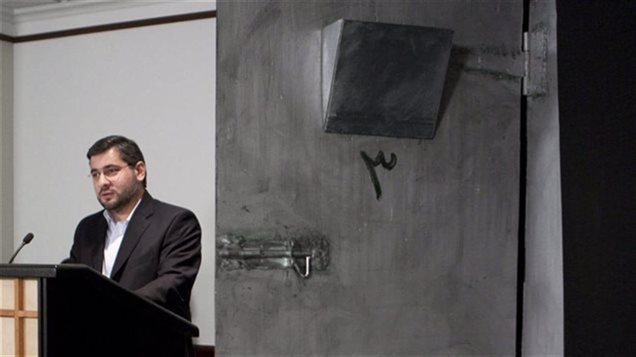 Abdullah Almalki à côté d'une reconstitution de sa cellule syrienne (2009)