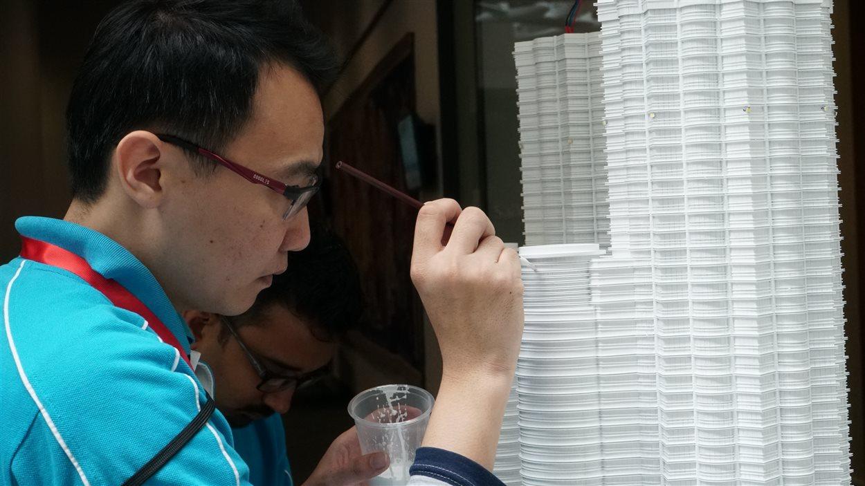 Deux artisans sont venus spécialement de la Malaisie pour restaurer une oeuvre de leur pays