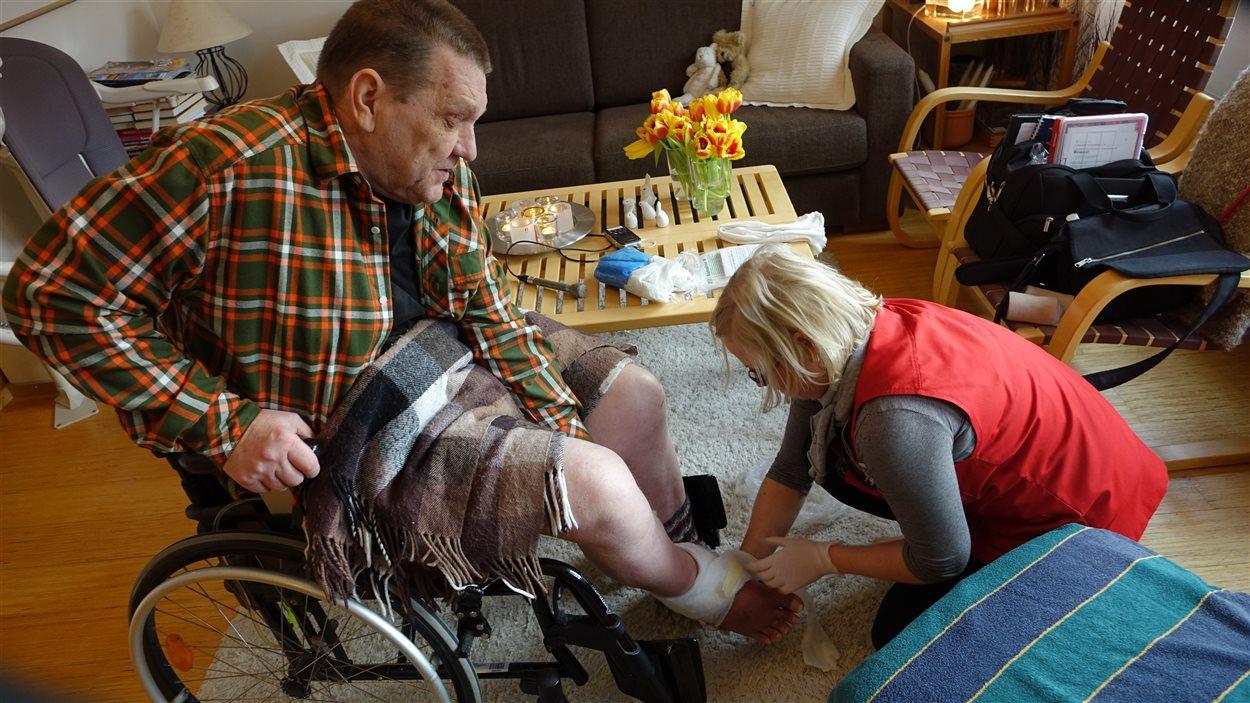 L'infirmière Sari Aaltonen soigne Leif Kauppilla, atteint de sclérose en plaques.