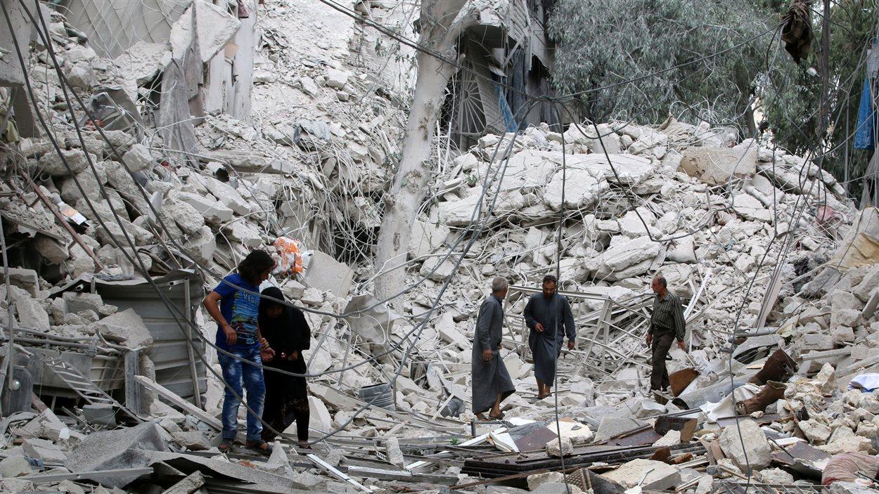 Dans le quartier rebelle de Tariq al-Bab, à Alep, des gens inspectent les dommages survenus en raison des frappes aériennes du régime syrien.