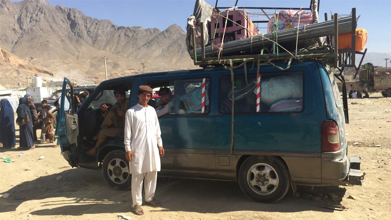 Des réfugiés retournent chez eux dans une camionnette remplie à ras-bord