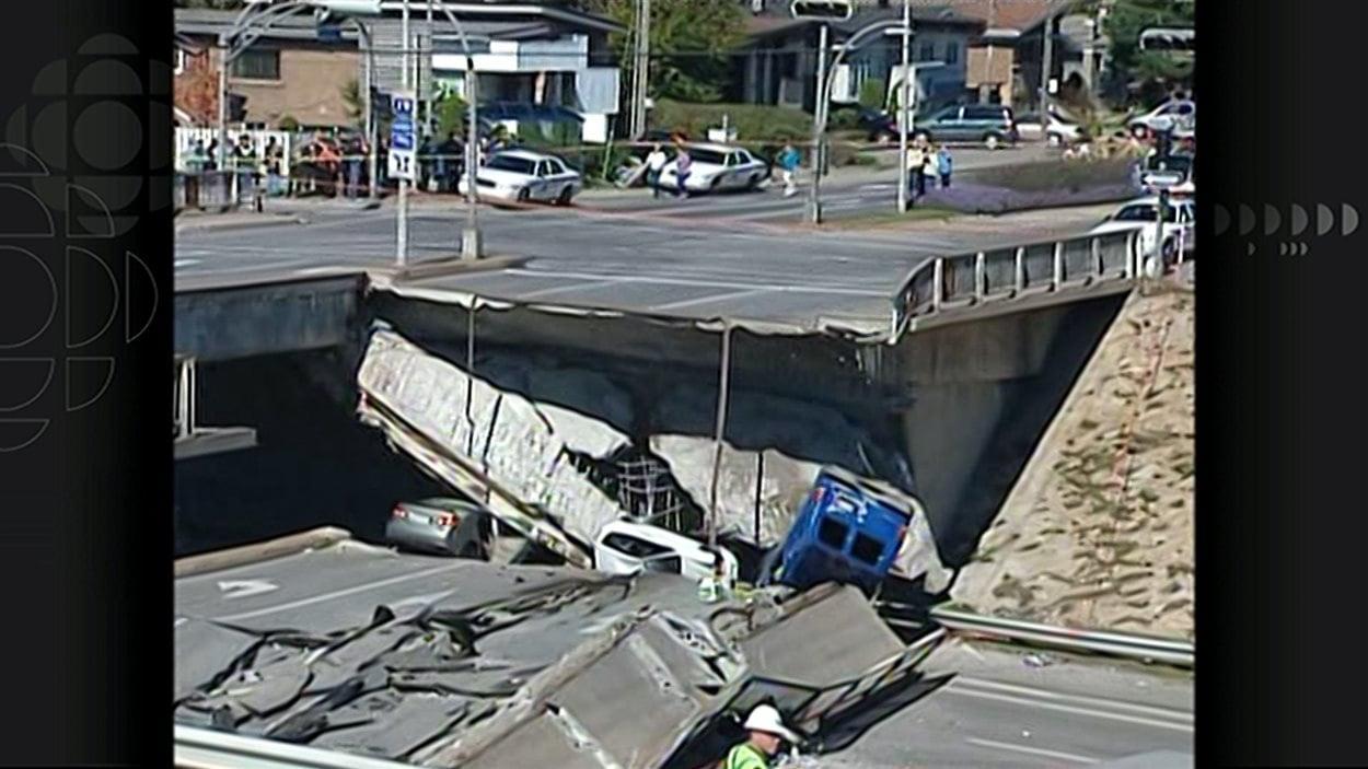 Plusieurs véhicules, dont une camionnette bleue, sous les décombres du viaduc de la Concorde