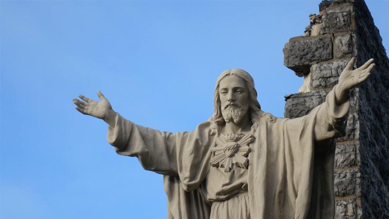 Une statue de Jésus trône devant les ruines de l'église.