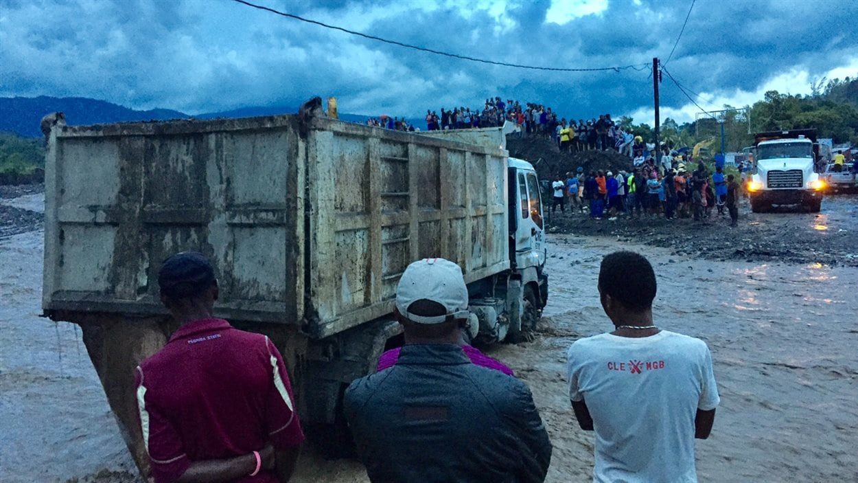 Des véhicules et des piétons peuvent maintenant traverser la rivière de boue à l'endroit où le pont s'est effondré, à Petit-Goâve. Le sud-ouest n'est plus coupé du monde.