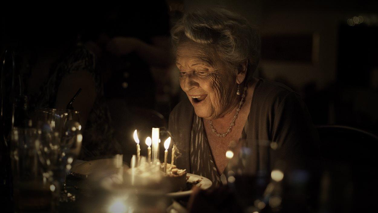 Une dame âgée souffle des bougies