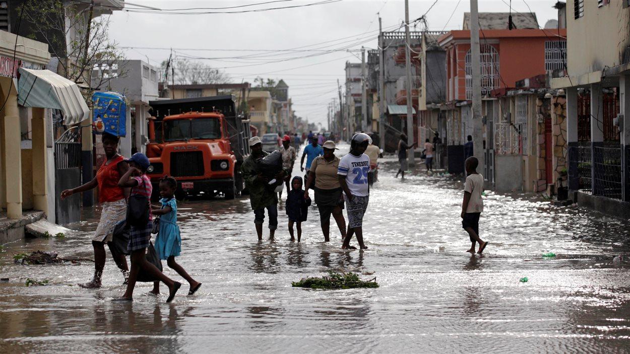 Des Haïtiens marchent dans la ville Les Cayes après le passage de l'ouragan Matthew.