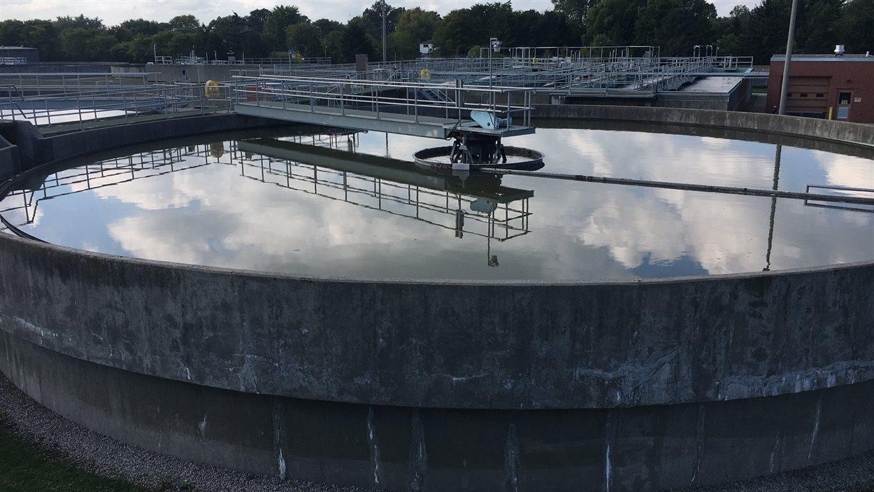 De l'eau repose dans un bassin à ciel ouvert qui est en train d'être décontaminée biologiquement