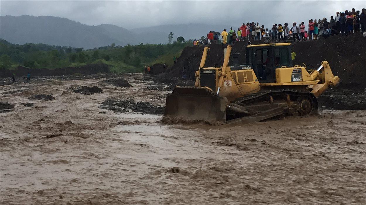 À Petit-Goâve, des travailleurs sont à pied d'oeuvre pour créer un pont temporaire à l'aide de roches.