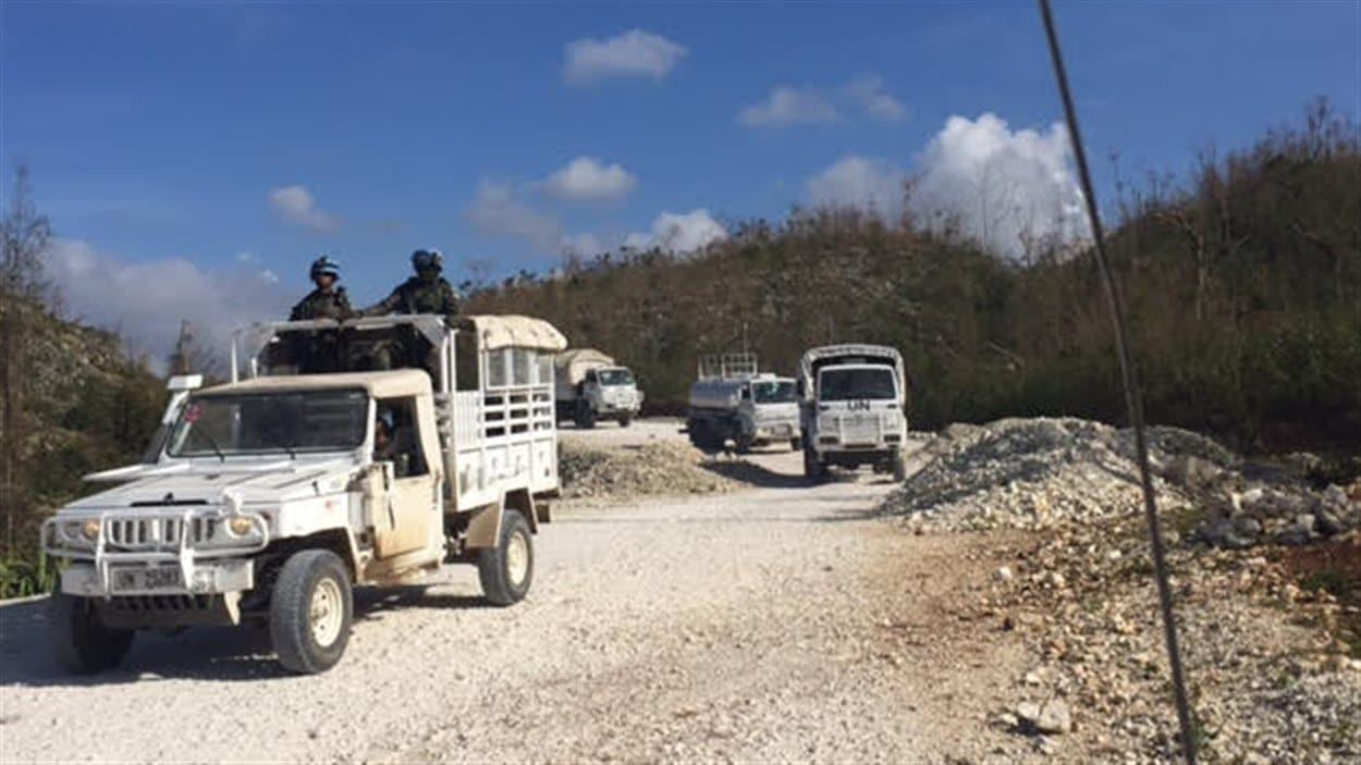 Un convoi de l'ONU circule sur la route, qui était impraticable auparavant. Des camions d'aide ont pu emprunter la route qui mène à Jérémie pour la première fois, samedi.