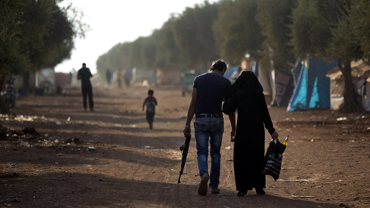 Un homme armé se déplace aux côté d'une femme dans un camp de réfugiés dans le nord d'Alep.