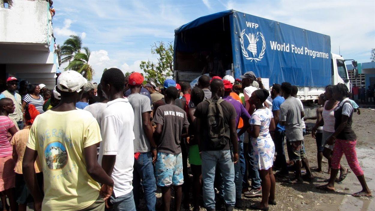 Les Haïtiens se ruent sur les camions du Programme alimentaire mondial pour obtenir des denrées.