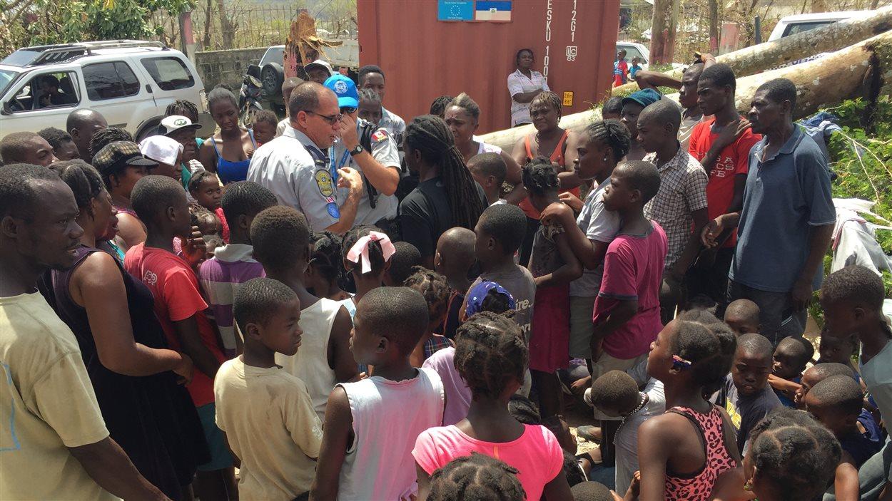 L'agent de la Sûreté du Québec Claude Desjardins, entouré d'enfants à Camp-Perrin, dans le sud d'Haïti