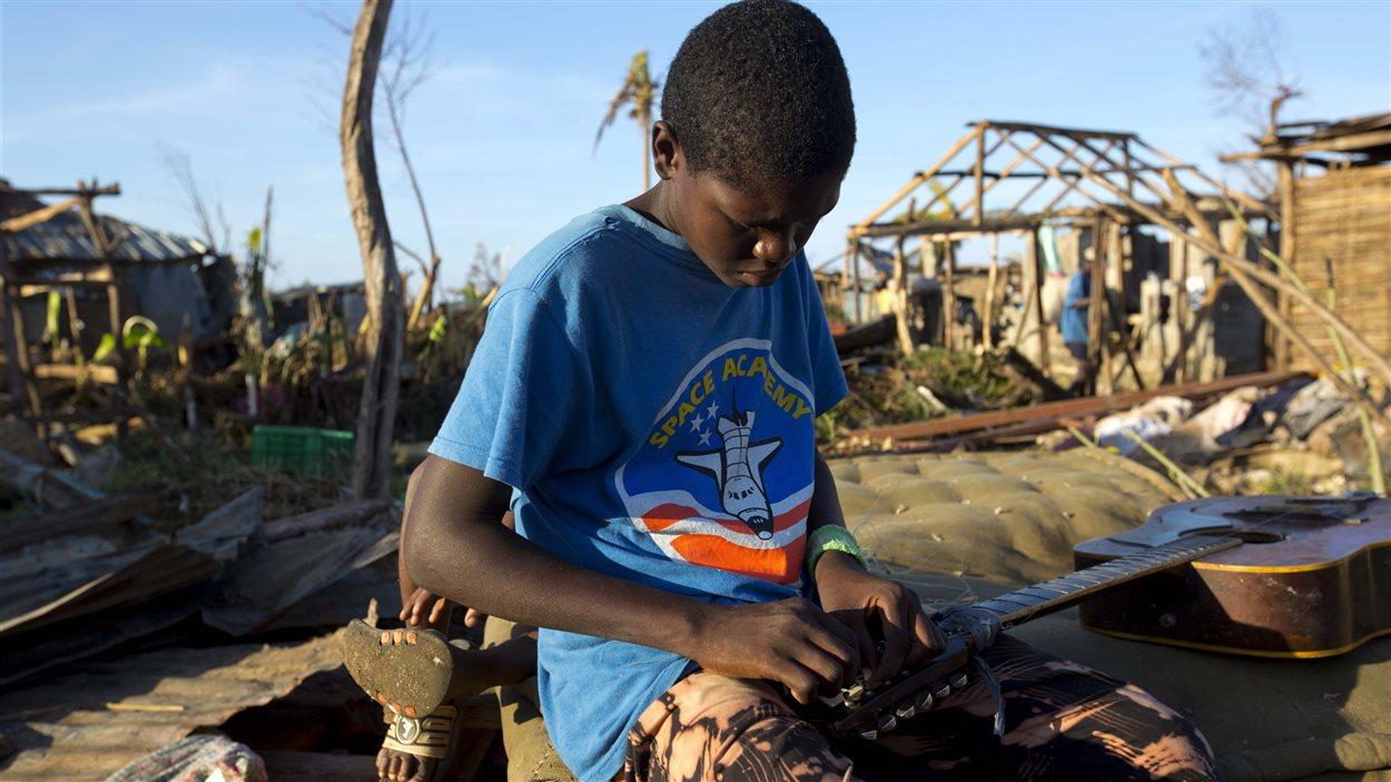 Un jeune garçon tente de réparer sa guitare à Hanse D'Hainault, en Haïti, le 11 octobre 2016, dans la dévastation causée par l'ouragan Matthew