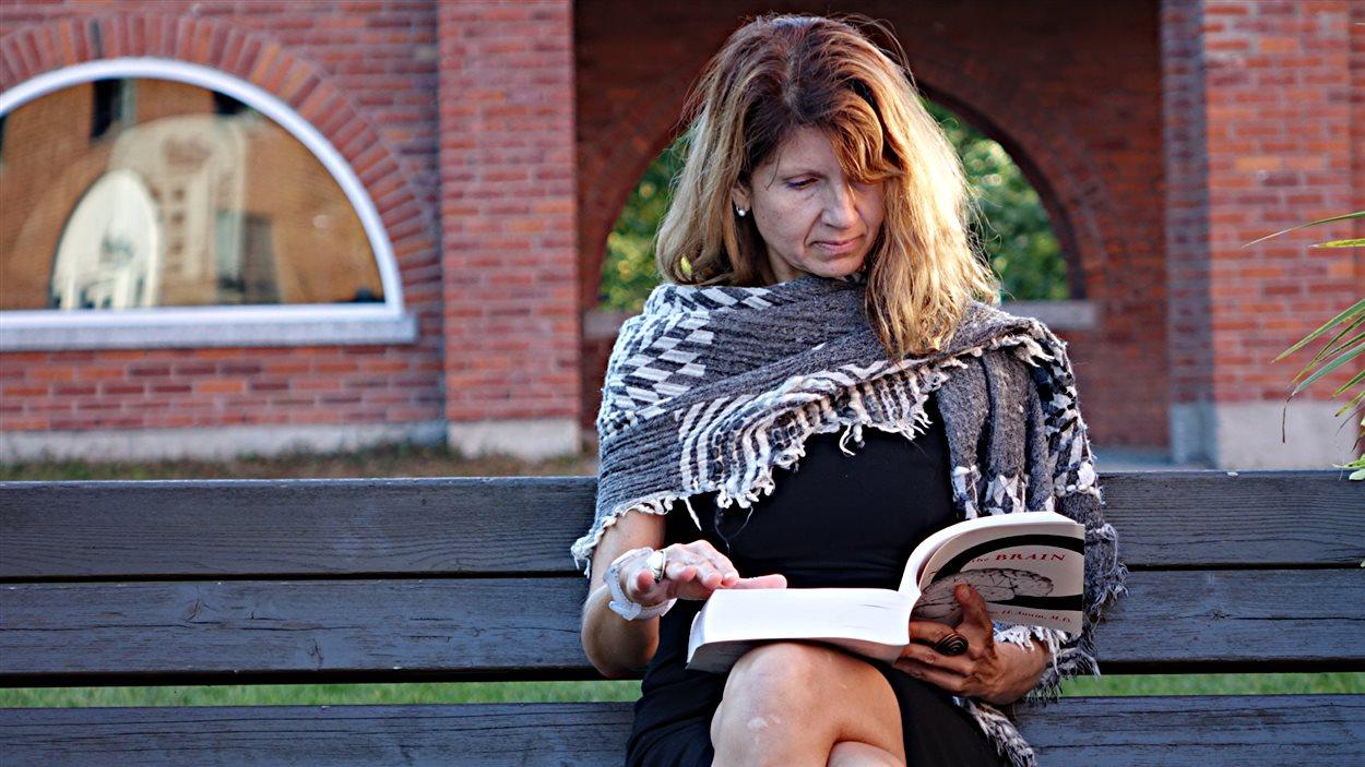 Adrianna Mendrek, professeure à l'Université Bishop's de Sherbrooke, lit sur un banc de parc